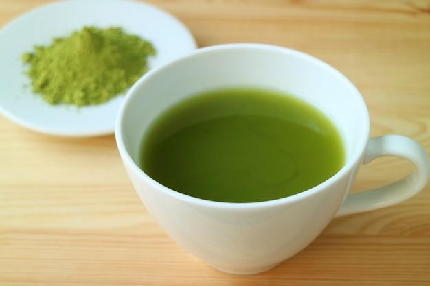 Schale heißer grüner tee matcha diente auf holztisch mit undeutlicher platte matcha-tee-pulver im hintergrund