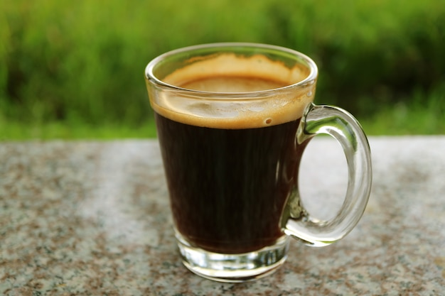 Schale heißer kaffee an der terrasse im freien mit undeutlichem vibrierendem grünem bush im hintergrund