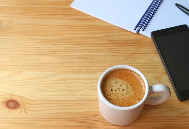 Schale heißer kaffee auf hölzernem arbeitsschreibtisch mit mobiltelefon und notizbuch, freier raum für text und design