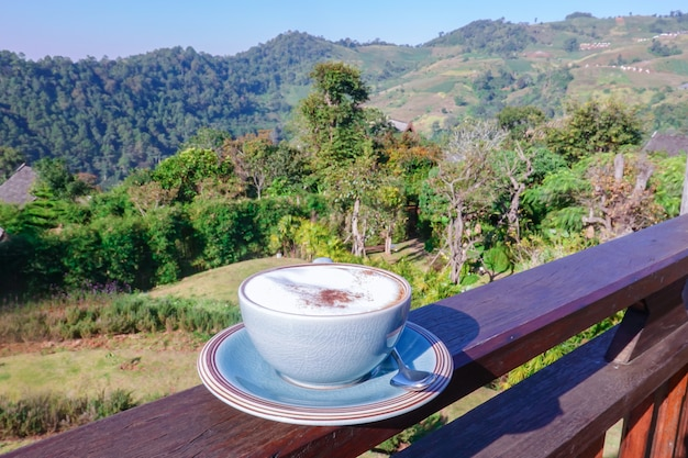 Schale heißer kaffee im café und sehen ansicht an der hohen spitze des hügels im feiertagsfestival.