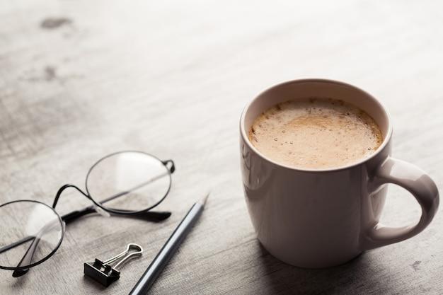 Schale heißer kaffee mit schaum, gläsern und bleistift auf der hölzernen schäbigen tabelle.