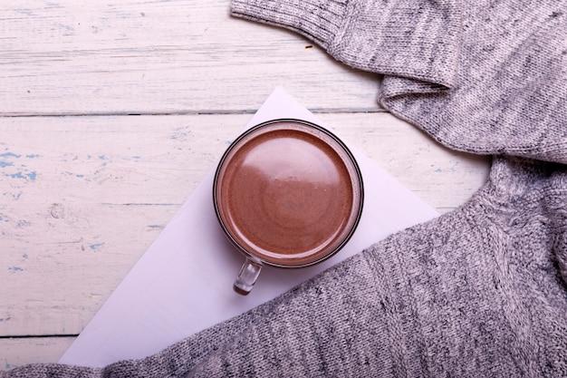 Schale heißer kaffee oder heiße schokolade auf rustikalem holztisch, warme strickjacke des nahaufnahmefotos mit becher, wintermorgenkonzept, draufsicht