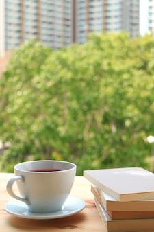 Schale heißer tee mit stapel büchern auf holztisch am fenster
