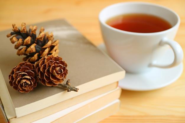 Schale heißer tee mit trockenen kiefernkegeln auf stapel büchern auf natürlichem farbholztisch