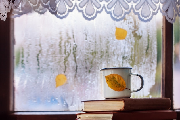 Schale herbsttee oder -kaffee und gelbblätter auf regnerischem fenster