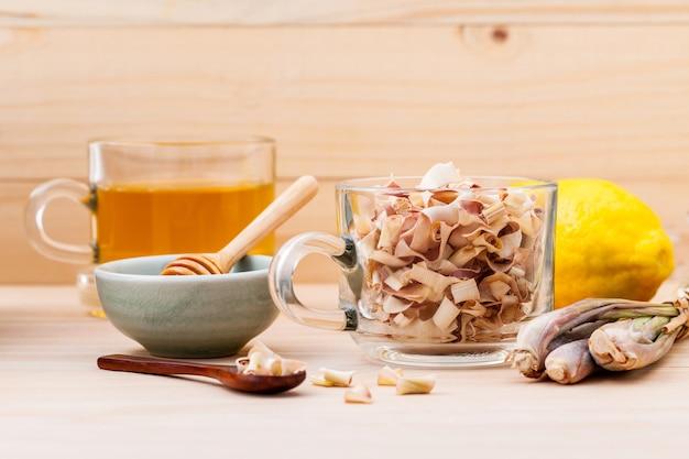 Schale kräutertee mit getrocknetem zitronengras, honig und zitrone auf hölzernem hintergrund.