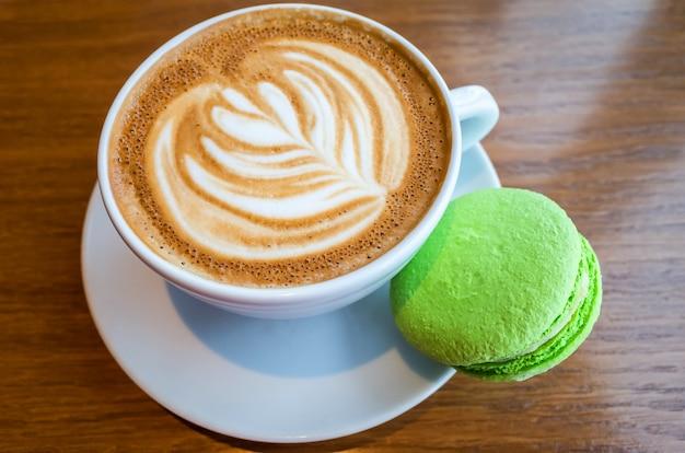 Schale latte mit einem muster und einer makrone auf einem holztisch in einer kaffeestube