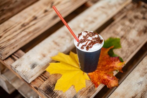 Schale lattekaffee mit einem cocktail des strohs und des herbstes färbte blätter auf einem hölzernen brett.