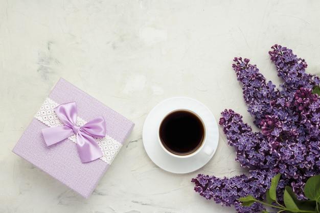 Schale mit einem kaffee, einer geschenkbox und einer schönen niederlassungsweißoberfläche