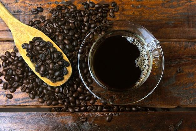 Schale mit frischem kaffee und gebratenen bohnen wurde auf rustikalem holztisch herum verschüttet. draufsicht