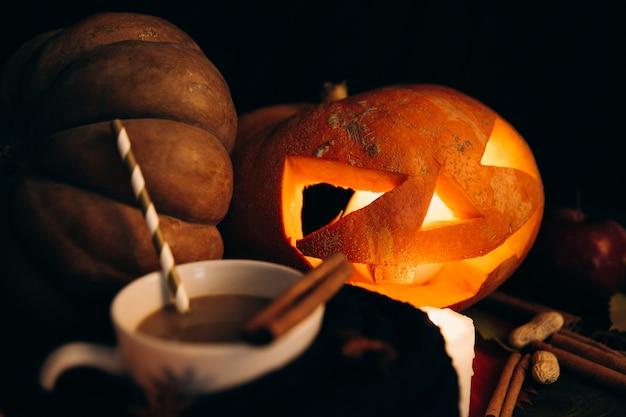 Schale mit heißer schokolade steht vor glänzendem beängstigendem halloween-kürbis