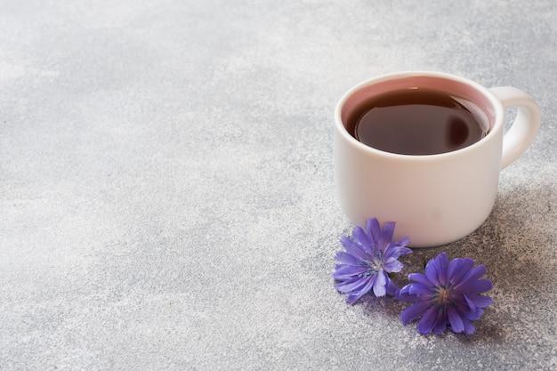 Schale mit zichoriengetränk und blauen zichorienblumen auf grauer tabelle