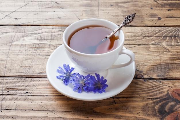 Schale mit zichoriengetränk und blauen zichorienblumen auf holztisch. kopieren sie platz.