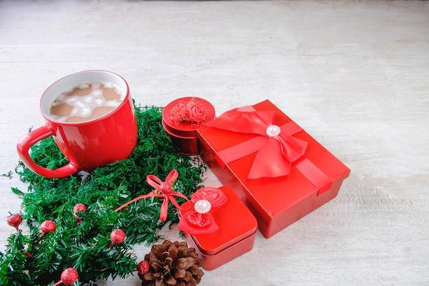Schale roter schokoladenkakao und rote geschenkbox mit weihnachtsbaum auf weißem hintergrund