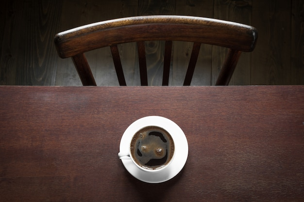 Schale schwarzer kaffee auf arbeitsholztisch