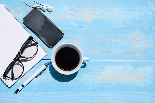 Schale schwarzer kaffee und intelligentes telefon mit büroartikel