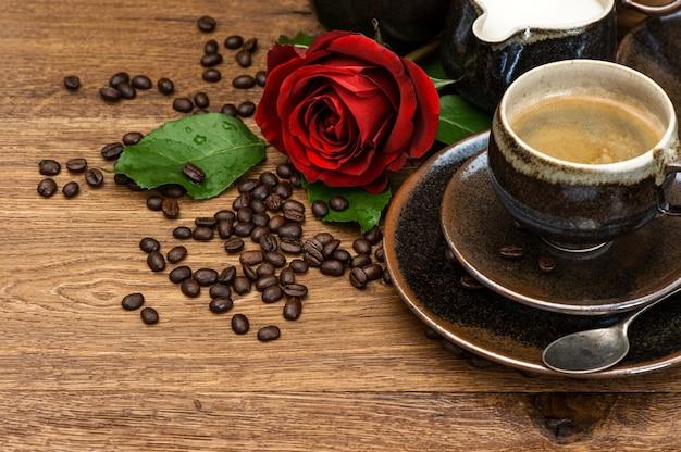 Schale schwarzer kaffee und rotrosenblume auf hölzernem hintergrund