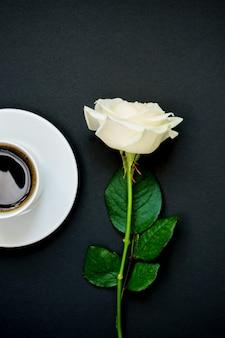 Schale schwarzer kaffee und weißrose auf schwarzem