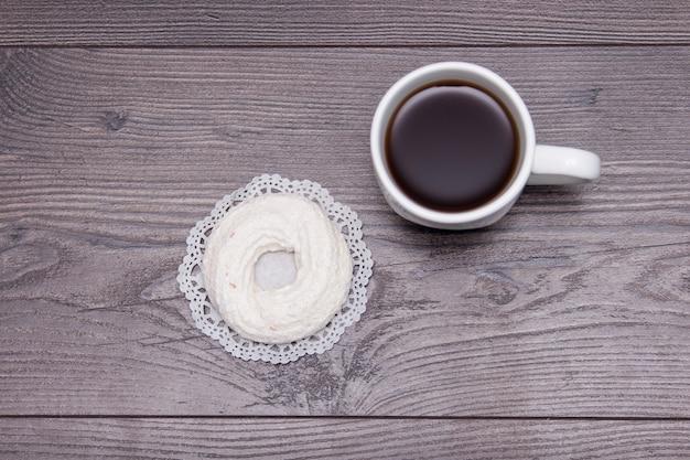 Schale schwarzer tee mit geschmackvollem köstlichem merengue auf dem braunen holztisch, draufsicht