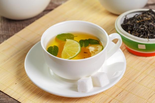 Schale schwarzer tee mit tadellosen blättern auf einem holztisch