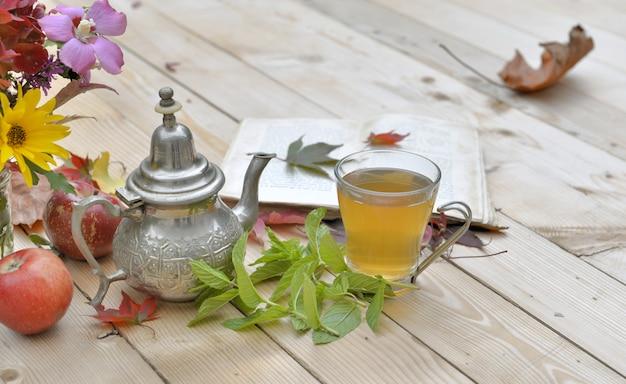 Schale tadelloser tee mit blumen und tadellosem blatt auf einer tabelle