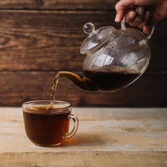 Schale warmer tee, der von einer teekanne gefüllt wird