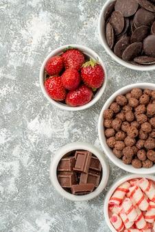 Schalen mit blick auf die obere hälfte mit süßigkeiten, erdbeeren, pralinen, müsli und kakao auf der rechten seite des grauweißen bodens