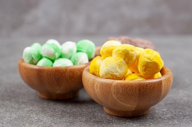 Schalen mit bunten bonbons auf marmoroberfläche