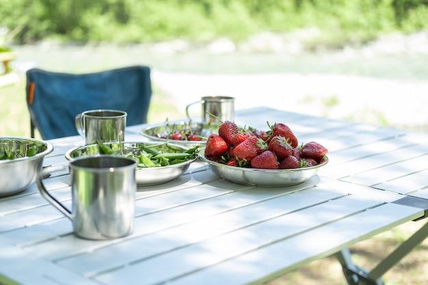 Schalen mit frischen erdbeeren, kirschen, grünen erbsen auf dem picknicktisch beim camping im sommer.