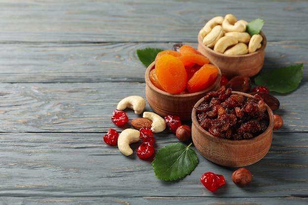 Schalen mit getrockneten früchten und nüssen auf grauem holztisch