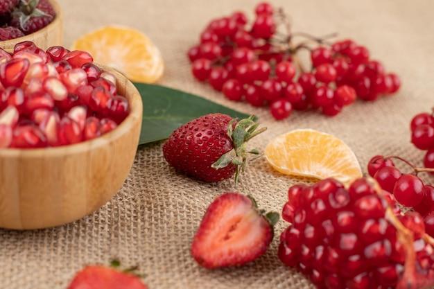 Schalen mit granatapfel und himbeere mit einer auswahl an früchten auf textilem hintergrund verstreut. hochwertiges foto