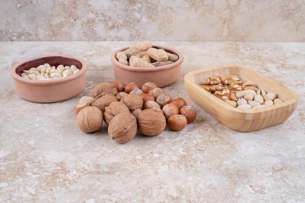 Schalen mit haselnüssen, erdnüssen, sonnenblumenkernen und popcorn auf marmoroberfläche
