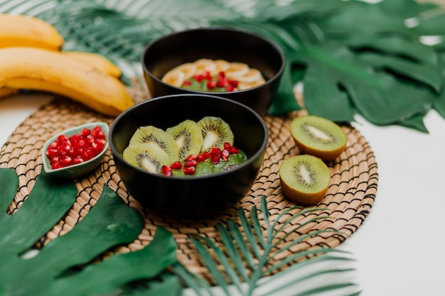 Schalen mit kiwi, müsli, granat, chia und avocado
