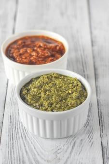 Schalen mit klassischem und sonnengetrocknetem tomatenpesto