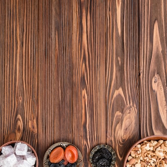Schalen mit lukum; erdnüsse und trockenfrüchte auf dem hölzernen hintergrund mit kopienraum für das schreiben des textes