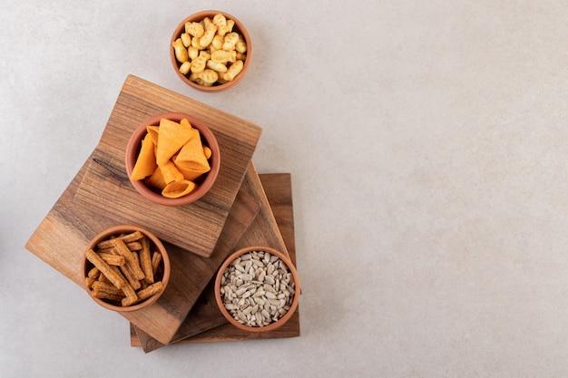 Schalen mit pommes, crackern und sonnenblumenkernen auf steinoberfläche.