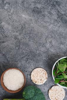 Schalen mit reiskörnern; puffreiskuchen; brokkoli und spinat auf grauem verwittertem hintergrund