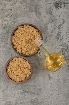Schalen mit rohen makkaroni mit olivenöl auf steinoberfläche.
