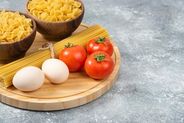 Schalen mit rohen nudeln, eiern und frischen tomaten auf marmoroberfläche.