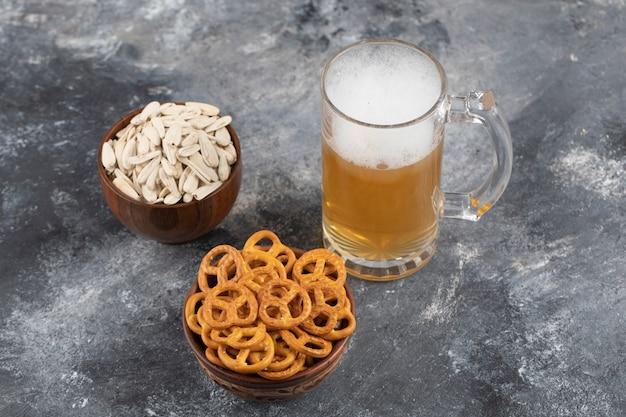 Schalen mit salzbrezeln, weiße sonnenblumenkerne mit schaumigem bier