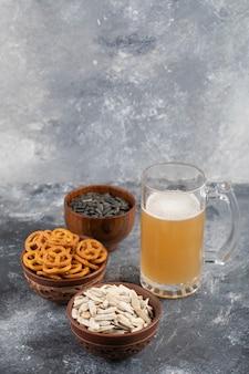 Schalen mit salzbrezeln, weißen und schwarzen sonnenblumenkernen mit schaumigem bier