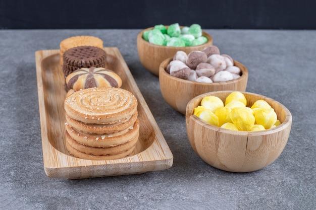Schalen mit süßigkeiten und ein kleines tablett mit keksen