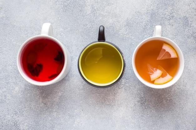 Schalen mit unterschiedlichem tee rot, grün und schwarz auf grauer tabelle