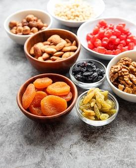 Schalen mit verschiedenen getrockneten früchten und nüssen auf einer grauen betonoberfläche
