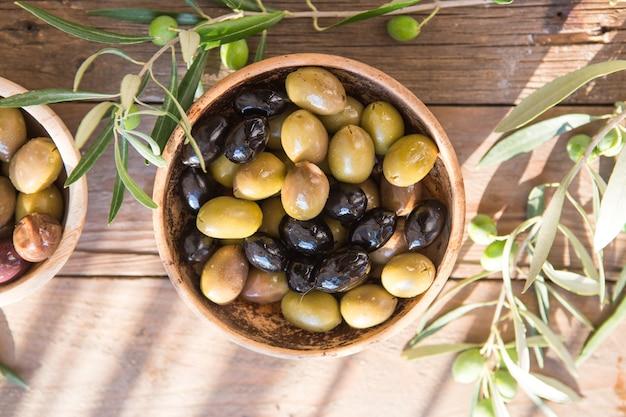Schalen mit verschiedenen olivensorten: grüne schwarze kalamata-oliven mit olivenöl