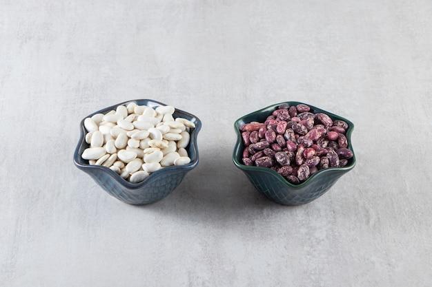 Schalen voller roher kidneybohnen auf steinoberfläche.