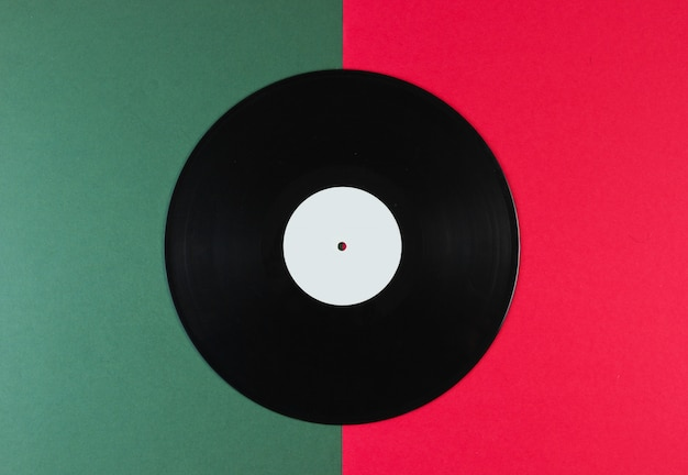 Schallplatte auf einer grün-roten oberfläche. retro-stil.