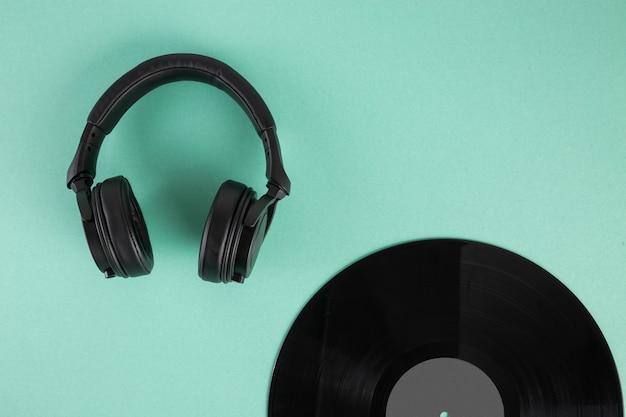 Schallplatte und kopfhörer auf abstraktem pastellhintergrund