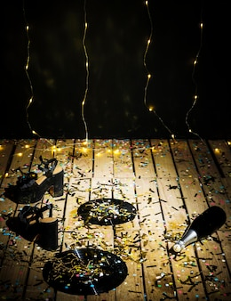 Schallplatten, frauenschuhe und eine flasche getränk zwischen konfetti in der nähe von wand
