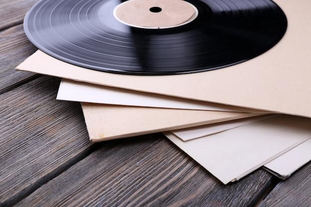 Schallplattenaufzeichnungen und papierabdeckungen auf hölzernem hintergrund